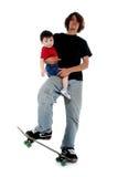 Garçon de l'adolescence et garçon d'enfant en bas âge sur la planche à roulettes Images libres de droits