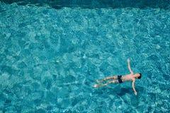Garçon de l'adolescence flottant sur l'eau dans une piscine dehors photo libre de droits