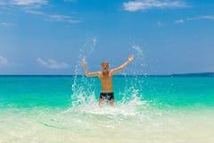 Garçon de l'adolescence heureux ayant l'amusement sur la plage tropicale Vacances d'été Image stock