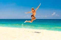 Garçon de l'adolescence heureux ayant l'amusement sur la plage tropicale Vacances d'été Images libres de droits