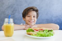 Garçon de l'adolescence heureux prenant le petit déjeuner à la maison Image stock