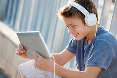 Garçon de l'adolescence mignon avec les écouteurs et la tablette. Photos stock