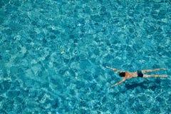 Garçon de l'adolescence nageant sous l'eau dans une piscine dehors photographie stock libre de droits