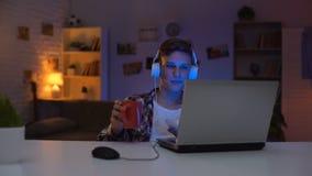 Garçon de l'adolescence observant l'exposition drôle sur l'ordinateur portable, mangeant des casse-croûte au temps libre, week-en banque de vidéos
