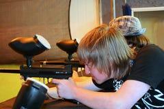 Garçon de l'adolescence orientant le canon de Paintball Photos stock