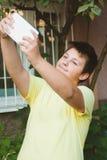 Garçon de l'adolescence prenant la photo de selfie avec le comprimé de smartphone Photo libre de droits