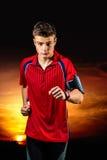 Garçon de l'adolescence pulsant avec la montre intelligente au coucher du soleil Photo libre de droits