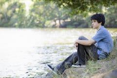 Garçon de l'adolescence s'asseyant par Lake Photographie stock