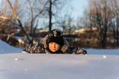 Garçon de l'adolescence se situant dans la neige image libre de droits