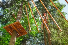 Garçon de l'adolescence sur un cours de cordes en parc d'aventure de cime d'arbre passant l'obstacle de cordage d'armement images stock