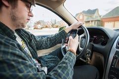 Garçon de l'adolescence textotant et conduisant dangereux distrait Photos stock
