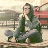 Garçon de l'adolescence triste dans la dépression se reposant sur le trottoir dans la rue de ville photographie stock