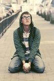 Garçon de l'adolescence triste dans la dépression se reposant sur le trottoir dans la rue de ville photos stock
