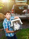 Garçon de la campagne avec le chat dans le transporteur allant voyager voiture Images libres de droits