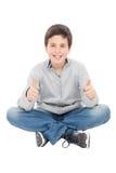 Garçon de la préadolescence de sourire s'asseyant sur le plancher indiquant correct Images stock