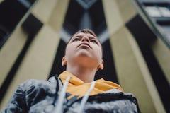 Garçon de la préadolescence sur une rue dans une grande ville à côté seul d'un gratte-ciel photo stock