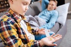 Garçon de la préadolescence tenant des pilules pour son père malade Image libre de droits