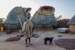 Garçon de la tribu de Tata Somba ou des personnes de Tammari avec les vêtements déchirés se tenant sur le toit du bâtiment de bou Photographie stock