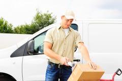 Garçon de livraison se tenant à côté de son Van images stock