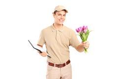 Garçon de livraison tenant un presse-papiers et des fleurs Photographie stock