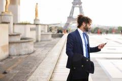 Garçon de mulâtre parlant avec l'amie par le téléphone près d'Eiffel Towe Images libres de droits