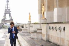 Garçon de mulâtre parlant avec l'amie par le téléphone près d'Eiffel Towe Photo stock