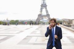 Garçon de mulâtre parlant avec l'amie par le téléphone près d'Eiffel Towe Photos stock