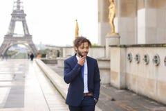 Garçon de mulâtre parlant avec l'amie par le téléphone près d'Eiffel Towe Images stock