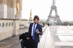 Garçon de mulâtre parlant avec l'amie par le téléphone près d'Eiffel Towe Image stock