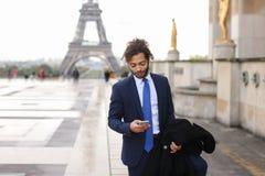 Garçon de mulâtre parlant avec l'amie par le téléphone près d'Eiffel Towe Photographie stock