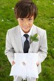 Garçon de page portant épousant Ring On Cushion photographie stock libre de droits