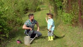 Garçon de papa et de fils arrosant la pousse sur le champ Enfance insouciant Garçon dans bottes de caoutchouc plantant sur le gis banque de vidéos