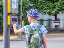 Garçon de petit enfant de vue de jour avec le bouton piétonnier de signal de pressing de sac à dos pour traverser la route britan images stock