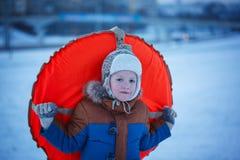 Garçon de portrait avec la tuyauterie dans la neige, hiver, concept de bonheur Images stock