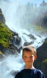Garçon de portrait sur le fond de cascade d'été Photo stock