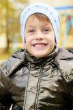 Garçon de quatre ans en parc d'automne utilisant un chapeau chaud Images stock