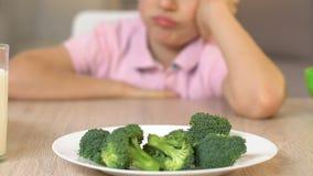 Garçon de renversement regardant le brocoli avec dégoût, refus pour manger, mode de vie végétarien clips vidéos
