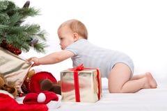 Garçon de Santa Baby atteignant pour le cadeau de Noël. Photographie stock
