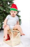 Garçon de Santa Baby s'asseyant sur le cadeau de Noël. Photographie stock libre de droits
