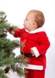 Garçon de Santa Baby se tenant à côté de l'arbre de Noël. Photographie stock libre de droits