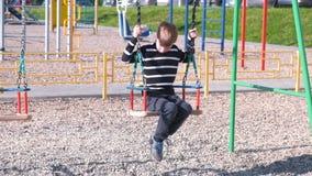 Garçon de sept ans balançant sur une oscillation sur le terrain de jeu clips vidéos