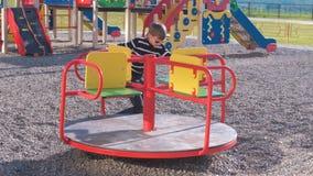Garçon de sept ans tournant sur le carrousel sur le terrain de jeu clips vidéos