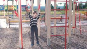 Garçon de sept ans tournant sur les anneaux gymnastiques sur le terrain de jeu banque de vidéos