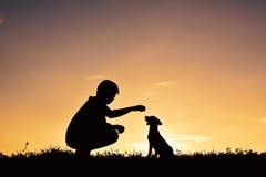 Garçon de silhouette jouant avec le petit chien Photo libre de droits