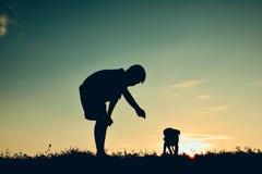 Garçon de silhouette jouant avec le petit chien Images libres de droits