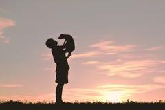 Garçon de silhouette jouant avec le petit chien Photographie stock libre de droits