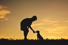 Garçon de silhouette jouant avec le petit chien Image libre de droits