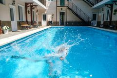 Garçon de six ans plongeant sous l'eau dans la piscine dans des troncs de natation, des nageoires et des lunettes de natation photos stock