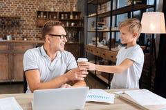 Garçon de soin donnant à son père travaillant par tasse de café Photos libres de droits