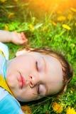Garçon de sommeil sur l'herbe Photographie stock